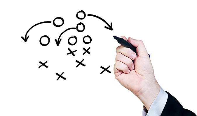 Man in a suit drawing out a diagram of football strategy.
